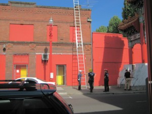 The red fire truck and yellow helmets of the firemen against this building!